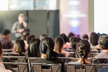 Rear view of Audience in the conference hall or seminar meeting which have speaker in front of the room on the stage, business and education concept