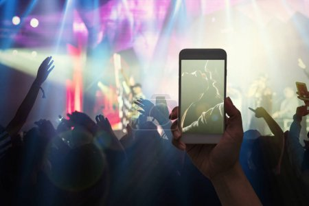 Female hand holding mobile smart phone taking video record or Live stream of Concert crowd with super star songer and silhouettes of Music fanclub with show hand action, musical and concert concept