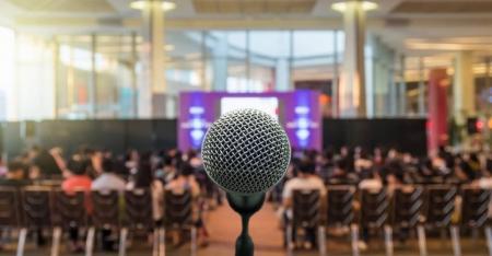 Photo pour Microphone sur le résumé floue la photo de la salle de conférence salle ou d'un séminaire avec les haut-parleurs sur le fond de scène et participant, concept de réunion d'affaires - image libre de droit