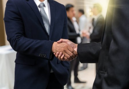 Business shaking hands of partner over the photo blurred of group of Businessman Corporate Colleagues Teamwork are discussing in modern workplace, business success and partnership concept