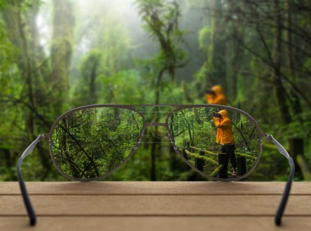 Conceptual image of rain forest focused in glasses lenses over the photo blurred of Traveller taking photo at Beautiful rain forest