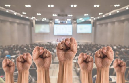 People Fists raised fighting for protest over the photo blurred of people in meeting room or hall background