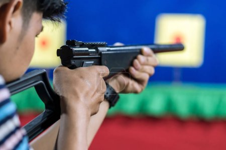 Rear view of man with his gun on shooting at the target in practice Shooting Range, sport and Soldier concept