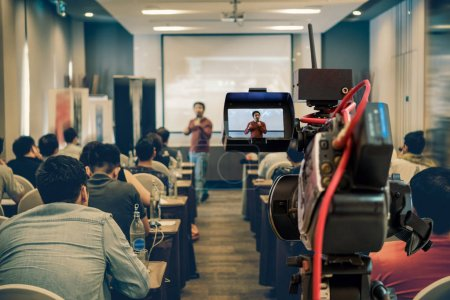Closeup Video recording the Asian Speaker with casual suit on the stage over the presentation screen in the meeting room of business or education seminar, event and seminar concept