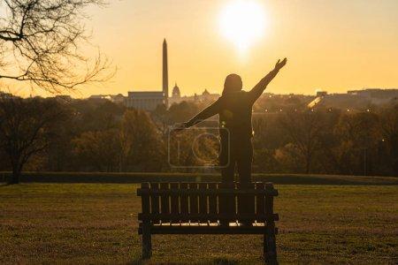 Photo pour Face arrière d'une femme asiatique debout et levant les mains pour réussir au-dessus du Washington Dc Landmark qui peut voir les États-Unis Capitol, washington monument et lincoln memorial au lever du soleil, - image libre de droit