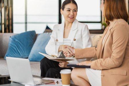 Photo pour Deux femmes d'affaires asiatiques bonheur Atteindre un accord en serrant la main ensemble après accord réussi le contrat d'affaires dans un bureau moderne ou un espace de coworking, concept de partenariat de succès - image libre de droit