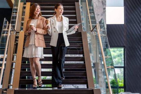 Photo for Two asian businesswomen walking and talking during coffee break in modern office or coworking space, coffee break, relaxing and talking after working time, business and people partnership concept - Royalty Free Image