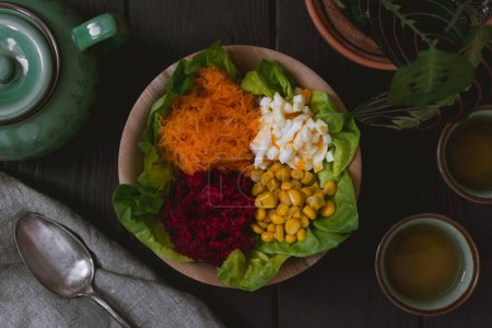 Photo for A high angle shot of a healthy salad with a side of sauces on a black wooden surface - Royalty Free Image
