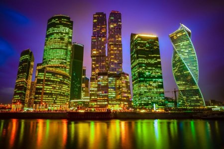 Photo for A fascinating low angle view of a city with illuminated skyscrapers on a purple background - Royalty Free Image