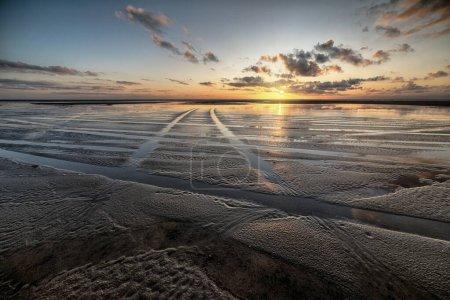 Photo pour Un magnifique décor du coucher de soleil reflété par une vasière sous un ciel nuageux - image libre de droit