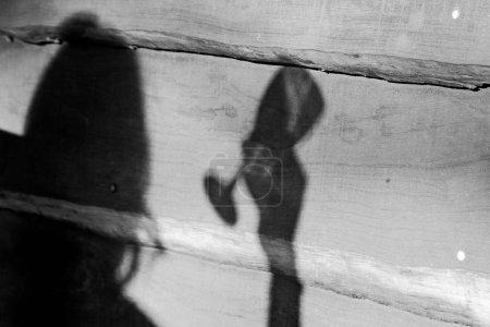 Photo pour Une chaude échelle de gris d'une personne ombragée tenant un verre de vin sur une surface en bois - image libre de droit