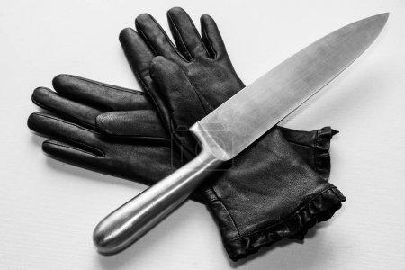 Photo pour Un coup de couteau métallique au-dessus de gants noirs sur une surface blanche - image libre de droit