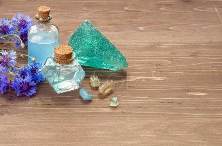 Photo pour Fleur de maïs bleue eau dans des bouteilles en verre et cristaux naturels pour la médecine alternative ou Spa sur fond en bois brun, copier l'espace - image libre de droit