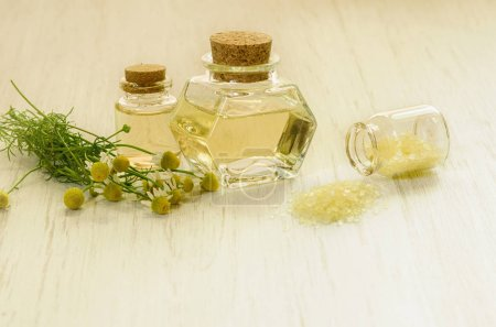 Photo pour Pharmacy chamomile water extract in bottle, yellow salt for SPA and fresh flowers as alternative or herbal medicine concept - image libre de droit