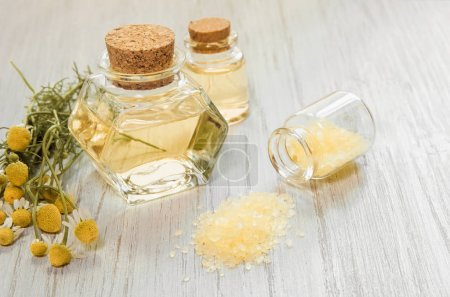 Photo pour Chamomile flower water. Glass bottles with infusion or hydrolate of pharmaceutical chamomile and bath or SPA salt on wooden white background - image libre de droit