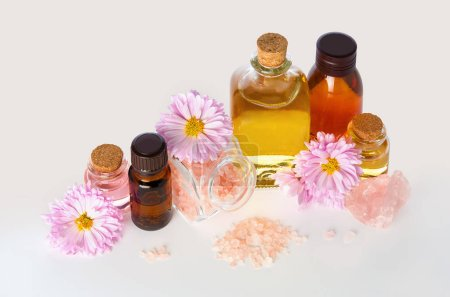 Photo pour Aromatherapy essential oil in medical glass bottles with chrysanthemum flowers and bath salt for SPA and Wellness on white background - image libre de droit