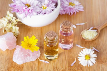 Photo pour Essential natural oil in medical glass bottles with chrysanthemum flowers and bath salt for SPA and aromatherapy on wooden background - image libre de droit