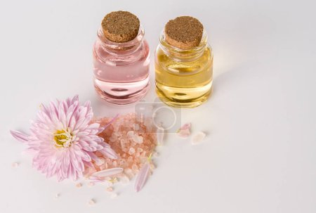 Photo pour Water flower or chrysanthemum essential oil in glass bottles with pink bath or SPA salt on white background - image libre de droit