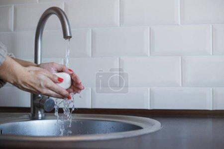 Photo pour La jeune femme se lave les mains avec du savon pour prévenir l'infection par le coronavirus. Les mains avec des ongles rouges sont soigneusement lavées pour maintenir l'hygiène. Sécurité des virus. Concept d'arrêt Covid-19 - image libre de droit