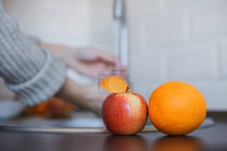 Photo pour Gros plan de la jeune femme lave les fruits pour prévenir l'infection par le coronavirus. Orange et pomme sont lavées à fond pour maintenir l'hygiène. Sécurité des virus. Concept d'arrêt Covid-19 - image libre de droit