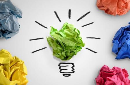 Photo pour Nouveau concept d'idée. Boules de papier de bureau colorées et croquis de l'ampoule - image libre de droit
