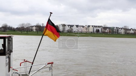 Photo pour Dusseldorf, Germany - February 20, 2020: flag of Germany on a ship on the Rhine. The German national flag on the back of a passenger ship flies in the wind. Liner at the time of Dusseldorf - image libre de droit