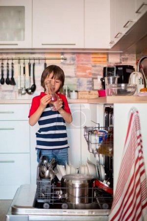 Preschool child, boy, helping mom, putting dirty dishes in dishw