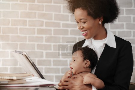 Photo for African american mother and businesswoman taking care of her child while working at home - Royalty Free Image