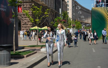 Photo pour Eurovision Village. Ukraine, Kiev. 05.05.2017. Editorial. Filles en costumes brillants, la publicité. Les gens marchent le long de Khreshchatyk Street, fan zone . - image libre de droit