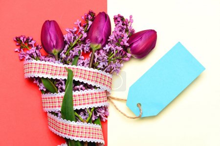 Bright bunch of flowers as gift with cyan message card