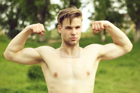 Sportsman with confident face expression shows his muscles