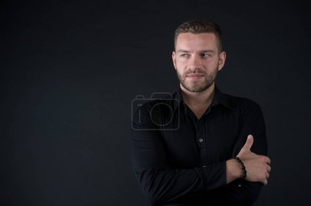 Photo for Barbershop, male beauty concept. Man with bearded face and stylish hair on dark background. Fashion, style, accessory. Macho in black shirt pose with folded hands, vintage filter, copy space - Royalty Free Image