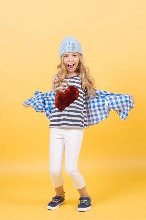 Photo pour Joyeux enfant sur fond orange. Fille sourire avec coeur rouge sur la chemise. Concept de Saint Valentin. Mode d'enfance, beauté, style. Tendance pastel punchy. - image libre de droit