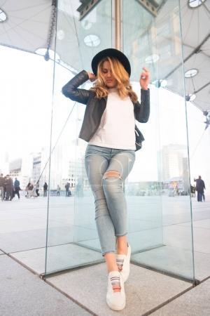 Photo pour Fille en chapeau, veste, jeans, baskets debout sur le mur de verre dans la défense, Paris. Mode, beauté, concept de style - image libre de droit