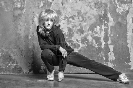 Photo pour Une femme porte une perruque avec un casque. Fille en costume de sport étirer jambe sur mur abstrait. Fitness, concept d'activité. Mode, beauté, regarde. Musique, technologie, divertissement, noir et blanc - image libre de droit