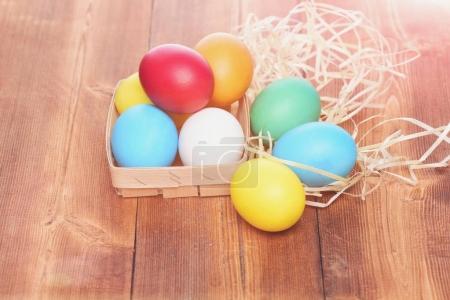 Photo pour Heureux Pâques vacances oeuf Pâques oeufs colorés peints dans des couleurs vives dans un panier en bois avec nid de paille sur fond de bois brun, célébration des vacances de printemps - image libre de droit