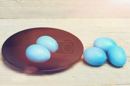 Photo for Hapyy easter holidays eggs and bunny future life, robin egg or eggshell blue, traditional easter painted food on black round plate in kitchen on grey wooden background, greeting - Royalty Free Image