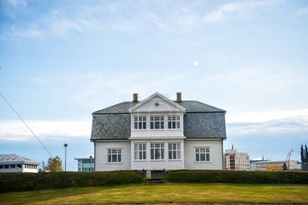 Photo for House with green lawn on blue sky in reykjavik, iceland. Architecture, structure and design. Village or small town building, real estate. - Royalty Free Image