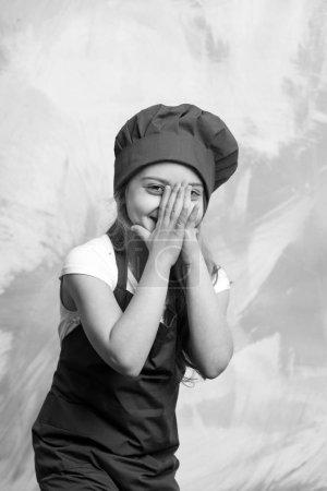 Photo pour Carrière, uniforme, rêve, profession et concept de profession. Petit cuisinier souriant sur un mur coloré. Enfant et enfance heureuse. Cuisiner et jouer. Fille en chapeau de chef et tablier . - image libre de droit