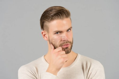 Photo for Bearded man touch beard with hand. Macho with stylish hair and healthy young skin. Guy with unshaven face and mustache. Beard grooming and hair care in barbershop. Skincare and mens beauty concept. - Royalty Free Image