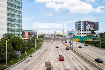 Photo for Miami, USA - October 30, 2015: highway or roadway with cars and skyscrapers on cloudy blue sky. Road with traffic signs for transport vehicles. Billboards on buildings. Public infrastructure concept. - Royalty Free Image