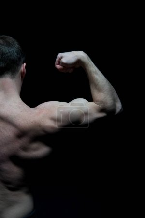 Photo for Man athlete with half torso, back view. Sportsman flex arm muscles. Bodybuilder show biceps and triceps. Workout and training activity in gym. Sport, power and bodycare concept. - Royalty Free Image