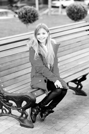 Photo for Girl in red coat sit on bench in park. Kid enjoy autumn day. Happy childhood concept. Child with blond long hair smile outdoor. Leisure, relaxation, lifestyle. - Royalty Free Image