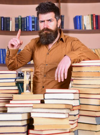 Photo pour Homme sur visage confiant se tient entre les piles de livres, alors qu'il étudiait à la bibliothèque, étagères sur le fond. Enseignant ou étudiant avec barbe s'élève à table avec des livres, défocalisés. Concept de bibliothécaire. - image libre de droit