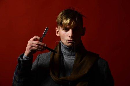 Photo pour Homme dans le style vintage tient lame de rasoir dans sa main. Salon de coiffure et concept de style. Styliste en costume et écharpe montrant rasoir sur fond rouge. Le gars tient un rasoir pointu dans la main droite . - image libre de droit