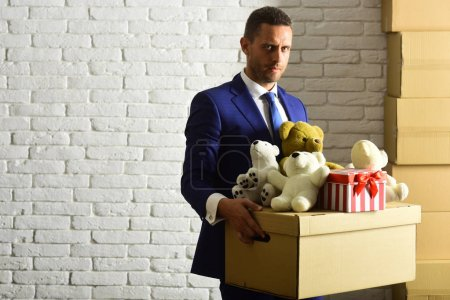 Photo pour L'homme au visage concentré fait un don. L'homme d'affaires porte un costume et une cravate intelligents. Gestionnaire tient boîte pleine de jouets et cadeau de Noël sur fond de mur de brique blanche. Concept d'entreprise et de volontariat - image libre de droit