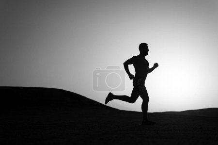 Photo for Man running silhouette on sunset background, young caucasian run in mountain - Royalty Free Image