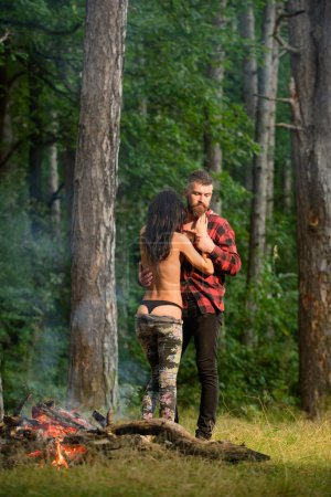 Photo for Couple full of desire going make love. Couple in love at picnic with fire in forest, trees on background, defocused. Love and sex concept. Man with woman undressing, nude woman in black lingerie. - Royalty Free Image
