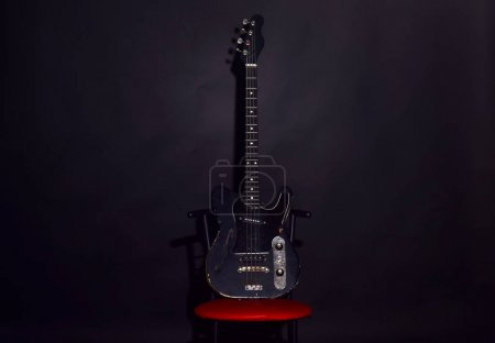 Photo for Guitar in deep black color on black background. Electric guitar stands on red chair. Musical instrument with four strings for playing metal or jazz music. Music and hard rock concept. - Royalty Free Image