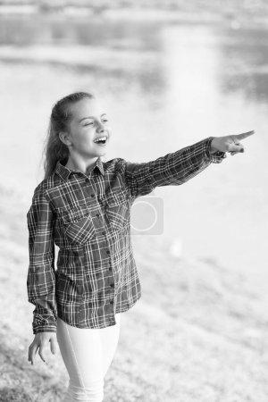 Photo pour Toujours été. Petite fille pointant du doigt la rivière sur le paysage estival. Adorable enfant avec de longs cheveux blonds dans un style décontracté à carreaux pendant les vacances d'été. Petit enfant portant une tenue d'été mode . - image libre de droit